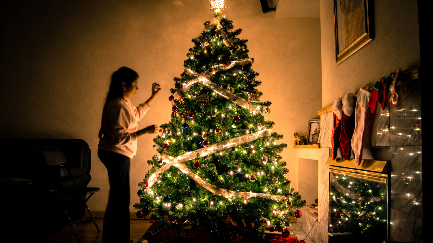 Girl decorating a lit Christmas tree in a semi-lit festively decorated room - used for the National Grid story 'The Christmas 'energy effect' revealed'