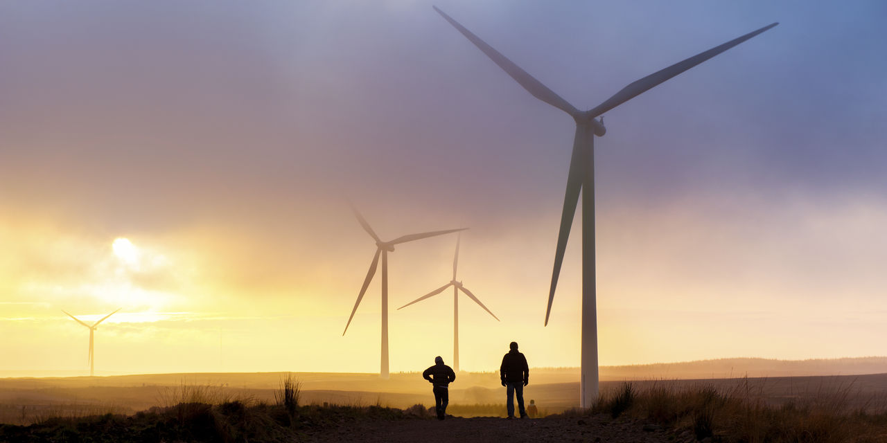 People walking across fields next to wind turbines - used for the National Grid story 'National Grid launches green bond to fund sustainability projects'