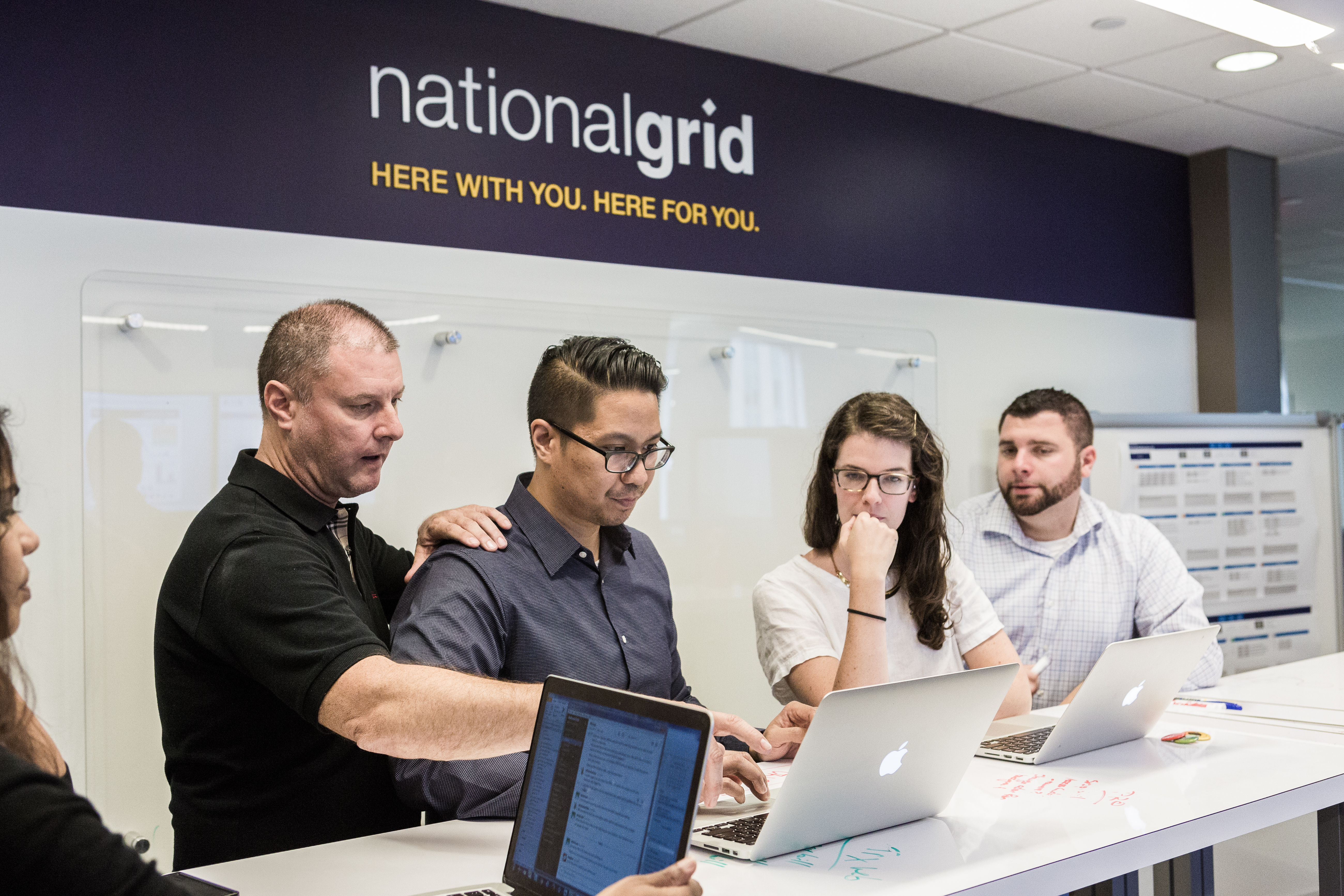 Five National Grid representatives working at a high desk with a white board in the background