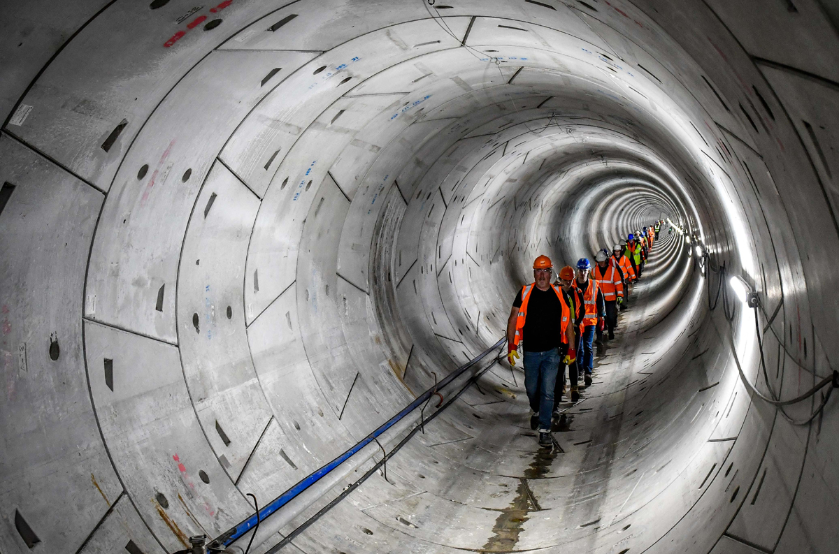 A line of people wearing hard hats and high-vis walking through the Humber Tunnel - used for the National Grid story 'Celebrating the completion of the Humber Tunnel'