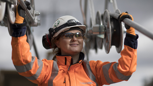 Female engineer wearing PPE holding National Grid high-voltage power cables