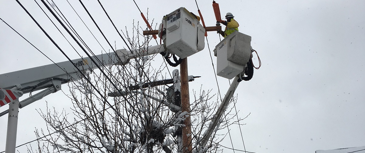National Grid lineworker fixing a power line in the snow in the US