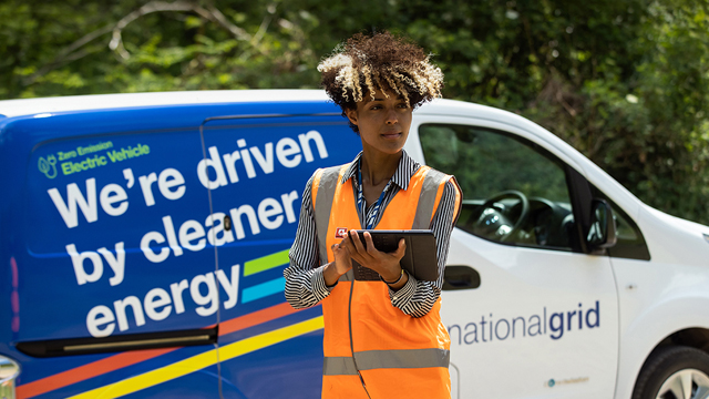 Woman wearing high-vis vest in front of National Grid EV van - used for launch of National Grid's Responsible Business Charter