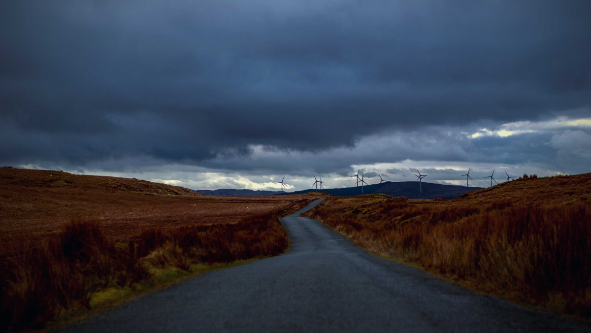 Empty road between brown moors under a stormy sky with wind turbines on the horizon - used for the National Grid story 'Riding the storm: how the ESO control room handles severe weather'