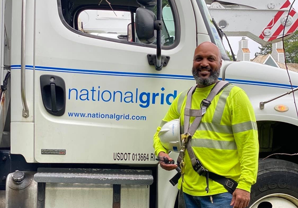 US Lineworker Donald Lopes in front of National Grid bucket truck