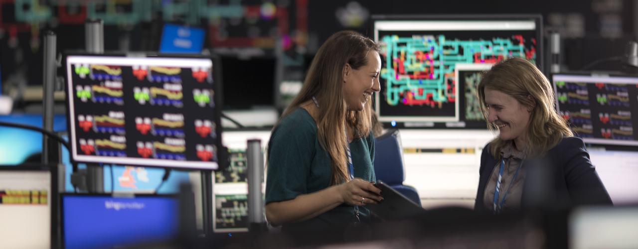 Two women standing in front of computer monitors in control room