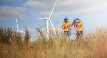 Man and woman standing in grassy field in front of windfarms, wearing hard hats and high-vis jackets with a survey camera - used for the National Grid story 'Now is the time to recruit a Net Zero Energy Workforce to power a greener future'