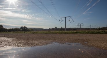A muddied wet patch of land with grass and electricity structures stretching into the background