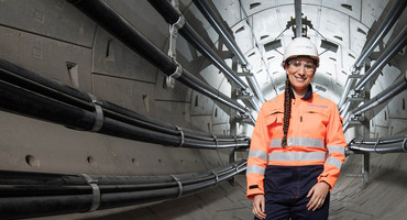 Female engineer wearing hard hat, safety goggles and overall inside London Power Tunnel - used for the National Grid story '400,000 new energy workers needed to power UK to net zero'