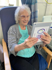 Elderly lady sitting in hospital chair holding electronic tablet - used for the story 'National Grid kicks off £1m coronavirus appeal to support NHS superheroes'