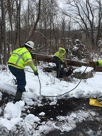 Two National Grid lineworkers digging in the snow in the US
