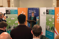 Rhian Kelly standing in front of business banner stands, addressing audience of men, women and photographers - used for the National Grid story 'All-party parliamentary group working together to deliver net zero'