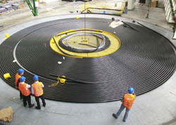 People wearing hard hats and high-vis jackets looking at high-voltage sub-sea cable coiled on the floor