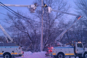 US lineworkers repairing lines from National Grid buckete trucks in snow storm