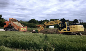 Digger and lorry in green field