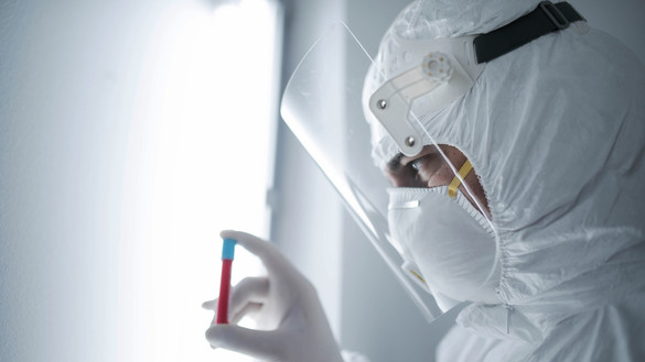 Person wearing full PPE holding blood vial used for National Grid 'Backing the quest for a COVID-19 vaccine' story