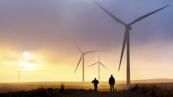 People walking across fields next to wind turbines - used for the National Grid story '200MW Crocker Wind Farm brings cleaner power online'