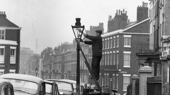 Early century black and white photo of man lighting street light for National Grid history