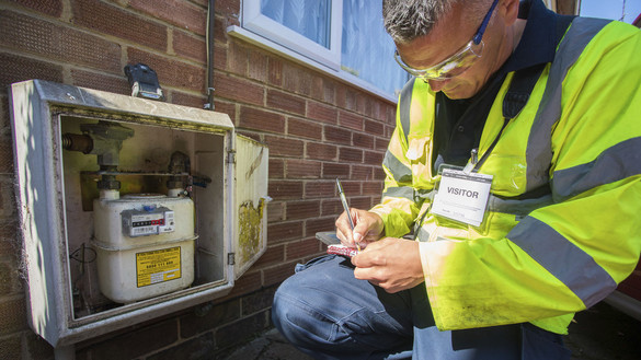 Metering engineer in high-vis jacket in front of gas meter - used for the National Grid story 'Why meters matter in a time of crisis'