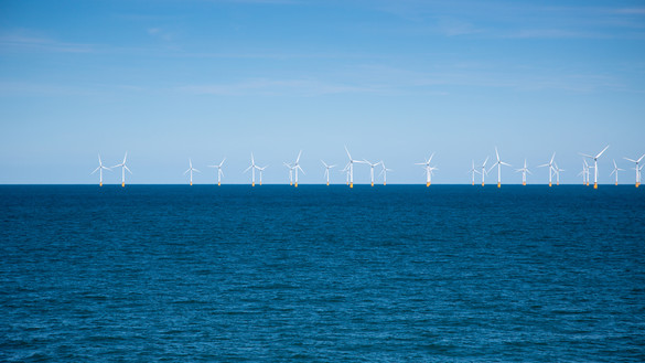 Wind farm in the distance at sea for National Grid 'Green loan speeds race to net zero' story