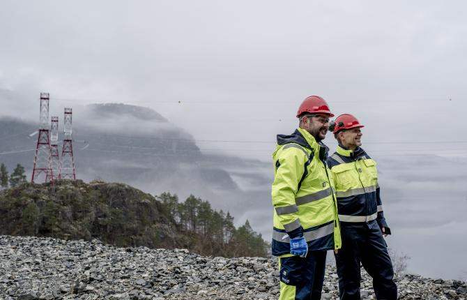 Two National Grid workers smiling with scenery, hilltops, and electricity structures in the background
