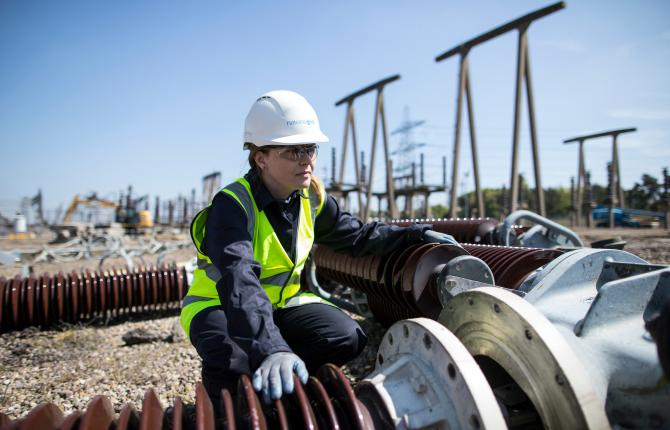 National Grid Senior Commercial Analyst Cirhan Truswell portrait with various industry equipment in the background