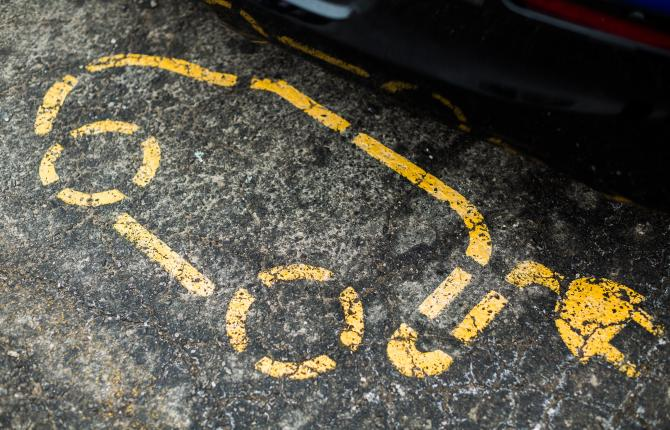 An electric car charging point symbol sprayed in yellow on black