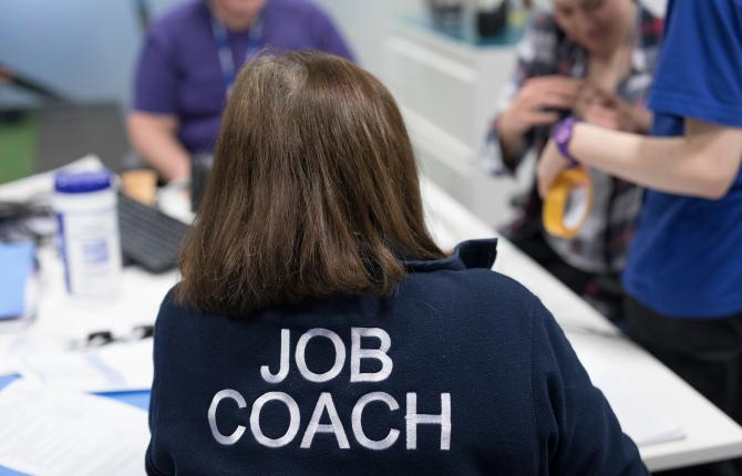 An individual wearing a Job Coach jumping while observing a young person's workshop experience