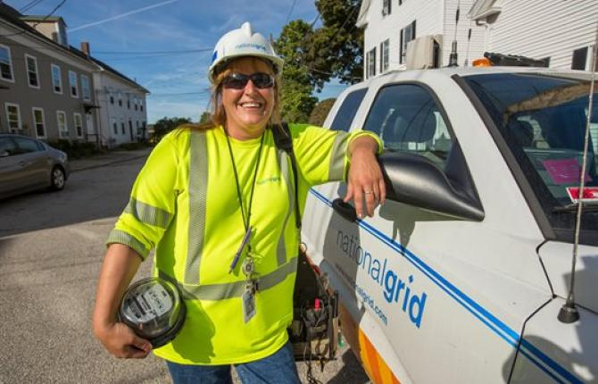 A National Grid employee leaning against a National Grid truck with a street in the background