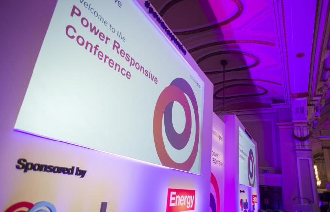 A large screen that reads 'Welcome to the Power Responsive Conference' inside a dimly lit room