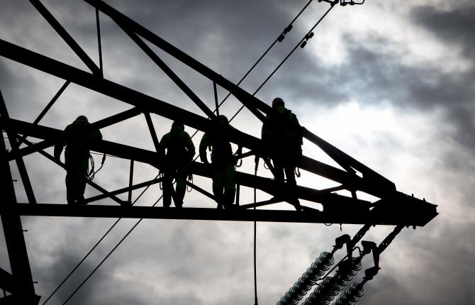 A silhouette of four individuals against an industrial structure with grey clouds in the background