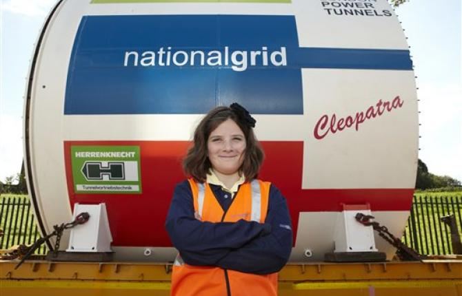 A young person standing in front of the National Grid London Power Tunnels Cleopatra part