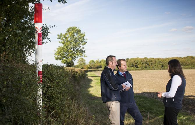 Three National Grid representatives standing in a field next to a red and white pillar
