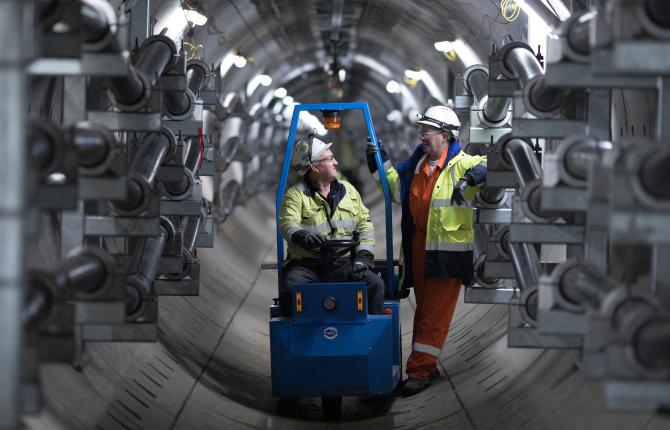 Two National Grid workers talking inside a tunneled structure