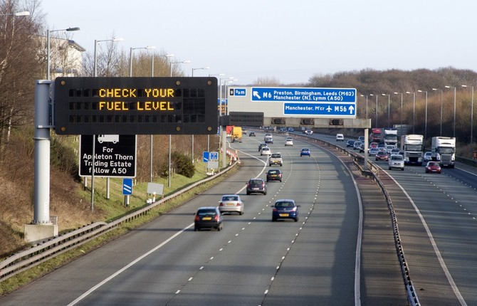 Motorway with 'check your fuel' sign for National Grid EV article