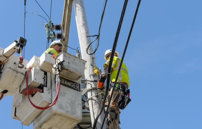 National Grid workers fixed to an electricity pylon with a blue sky in the background