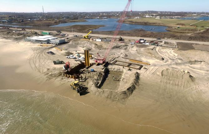 An aerial shot of construction work taking place on a beach with land and water in the background