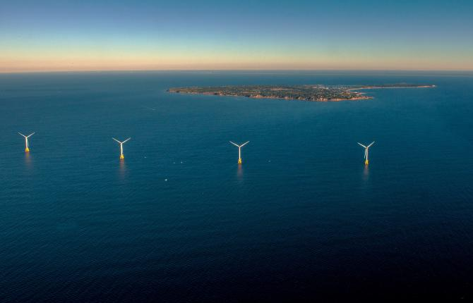 A seascape of dark blue ocean with an island in the background and several wind turbines appearing up from the water