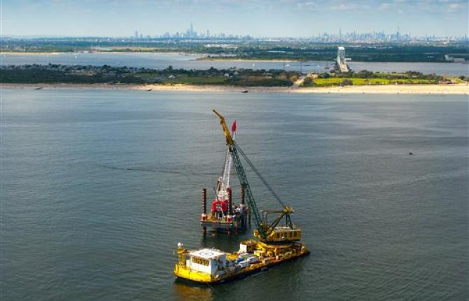 A bird's eye view of a gas rig in a body of water with the shoreline and a city-view in the background