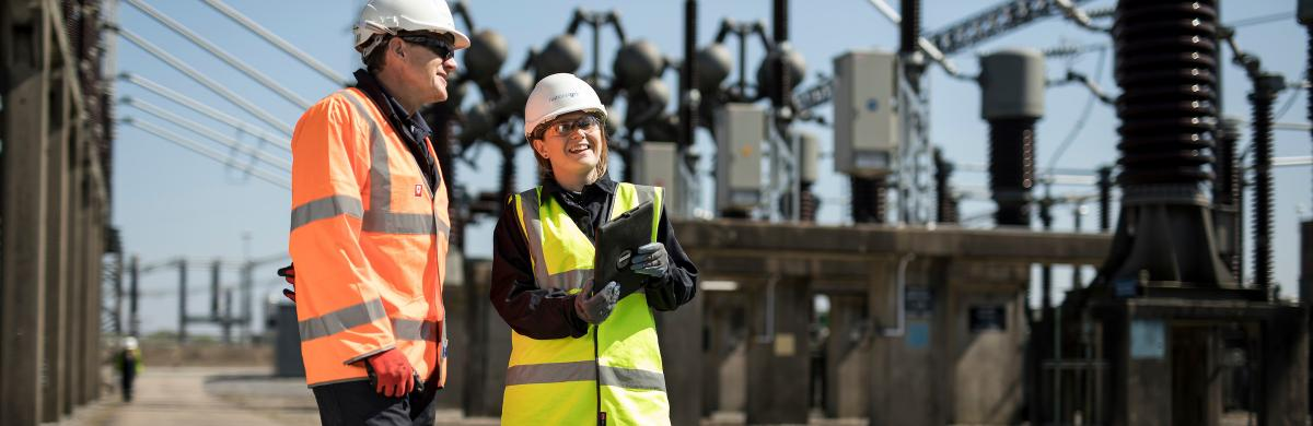 Two National Grid employees talking in front of an industrial framework