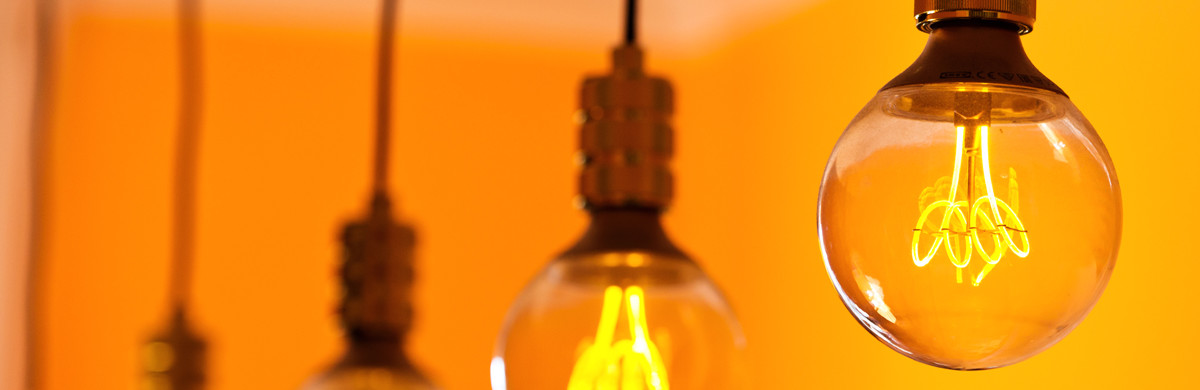 Row of lightbulbs hanging in a room with orange walls - used for the National Grid story 'Britain's electricity explained: new monthly report shows how we use power'