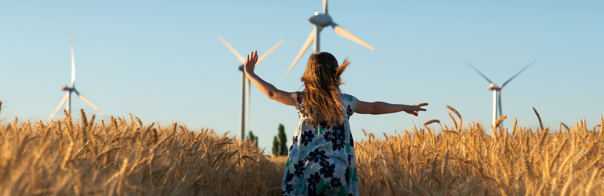 Responsibility - girl running in field with wind turbines in the background
