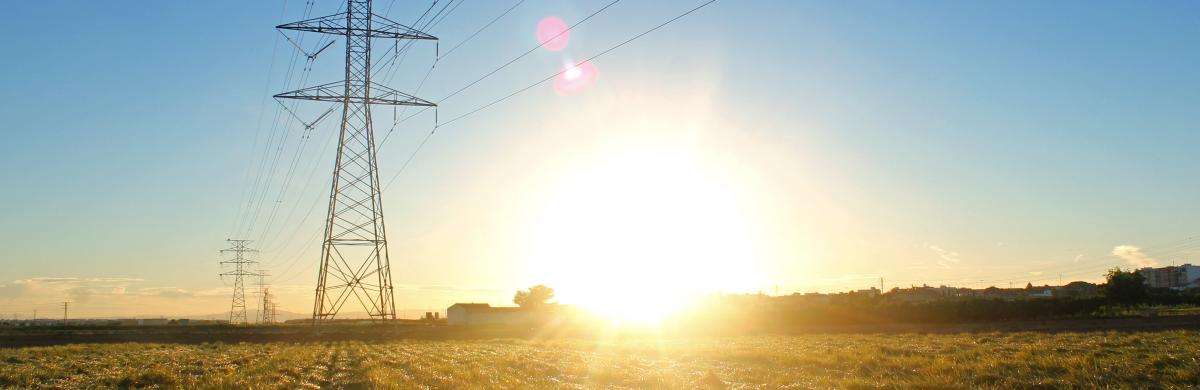 A field landscape with electricity pylons and overhead cabling and a bright sun setting in a blue sky