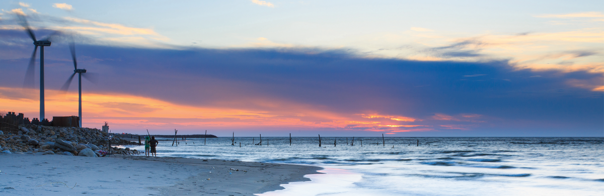 A beach landscape at sunset with wind turbines - Our climate commitment