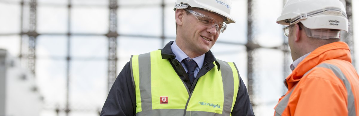 An image of National Grid CEO John Pettigrew and another man in safety gear in front of a gas holder