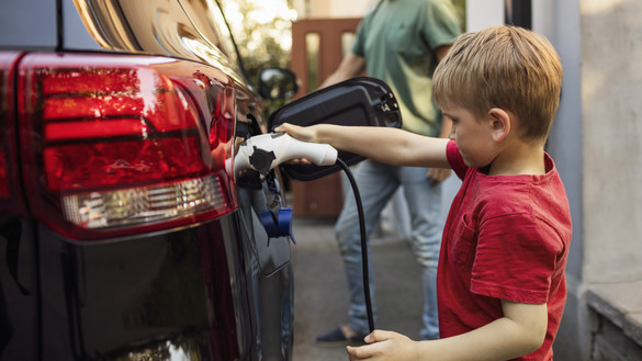 A child holding a fuel lead into a car