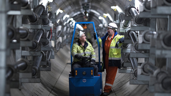 Two National Grid employees talking inside a grey tunnel space