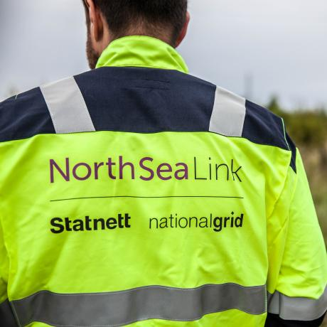 A National Grid worker facing away and wearing North Sea Link branded clothing with blurred scenery in the background