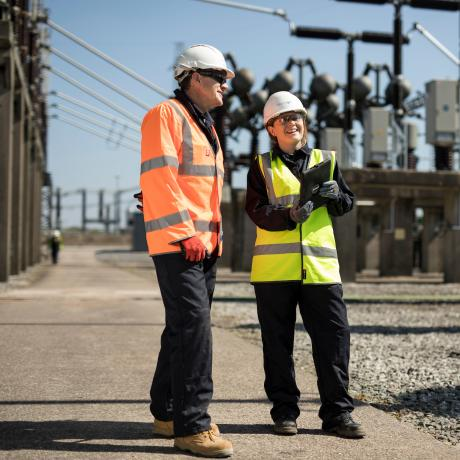 Two National Grid employees talking in front of an industrial framework - Cutting carbon and costs