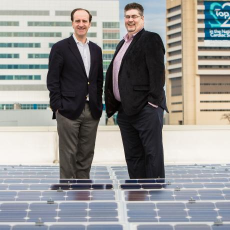 Two National Grid representatives standing in front of a building-skyline - a close up shot